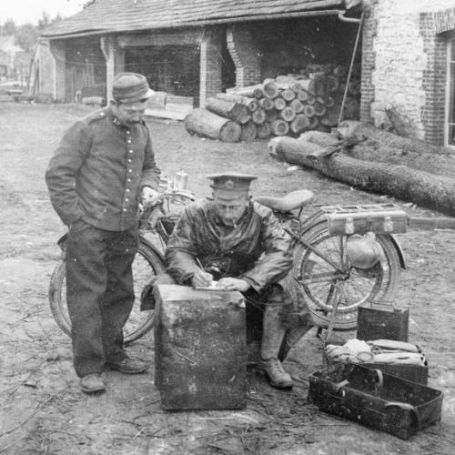 A British motorcycle dispatch rider takes a message in a Belgian village on 16 October 1914